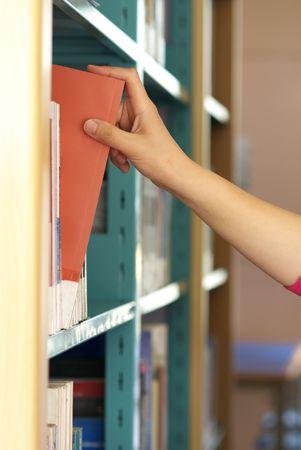 selecting books in library bookshelf