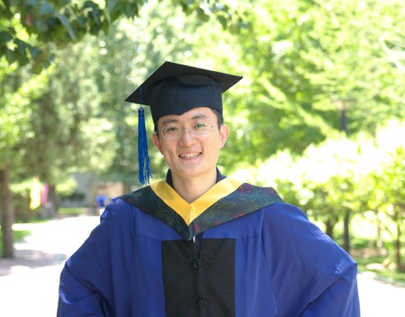 student wears gown on graduation day Imagens