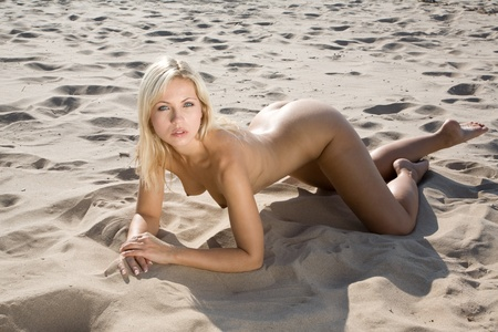 very sexy nude girl on the beach laying in the sun Stock Photo