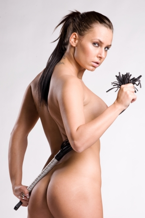 girl sexy nude: chica desnuda sexy con l�tigo en sus manos sobre fondo gris blanco claro Foto de archivo