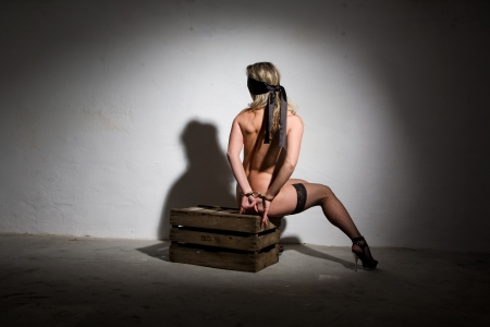 sexy beautiful nude girl blindfolded with a silk scarf and bound in a dungeon with handcuffs Stock Photo - 9169131