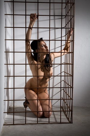 beautiful nude girl locked in cage in dark dungeon style Stock Photo - 9200815