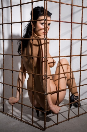 beautiful naked girl locked in cage in dark dungeon style Stock Photo - 9201021