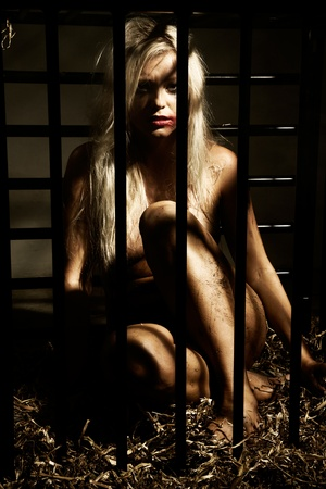 bondage art style with a beautiful nude slave girl locked in a cage with black bars and her naked body and make up is looking dirty Stock Photo - 10039387