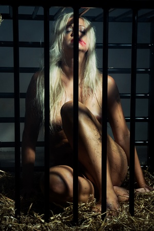 bondage art style with a beautiful nude slave girl locked in a cage with black bars and her naked body and make up is looking dirty Stock Photo - 10039398