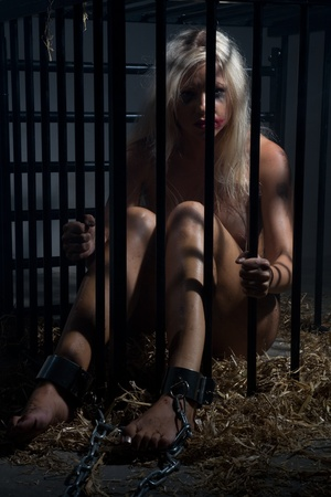 bondage art style with a beautiful nude slave girl locked in a cage with black bars and her naked body and make up is looking dirty and her feet are shackled with cuffs Stock Photo - 10039389