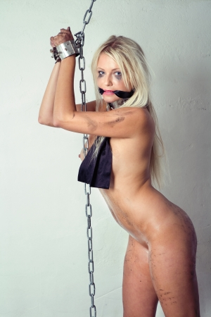 bondage art style with blond dirty woman cuffed in chains en gagged with silk scarf Stock Photo - 10039375