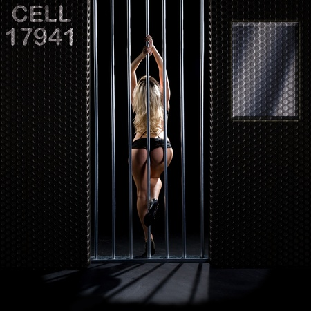 beautiful woman in black lingerie locked in a prison cell Stock Photo - 10765744
