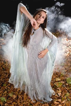 sorci�re sexy: sorci�re tr�s sexy habill�e en style gothique Halloween avec un �clat gr�ce � robe dans une for�t Banque d'images