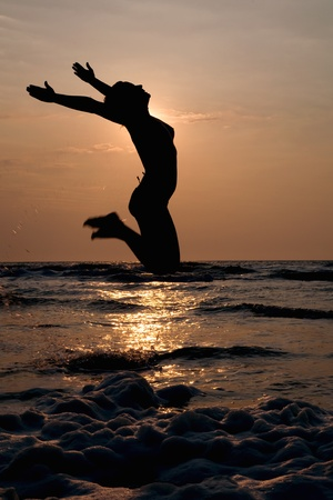 silhouette of a beautiful and sexy girl who  is  jumping in the ocean at  sunset photo