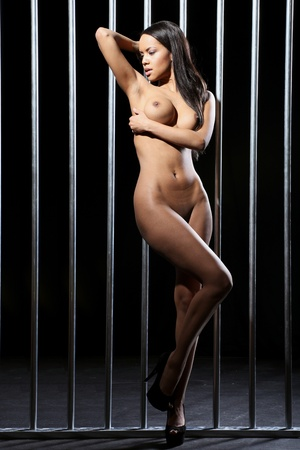 very beautiful nude model is standing in front of steel jail bars with a dark background