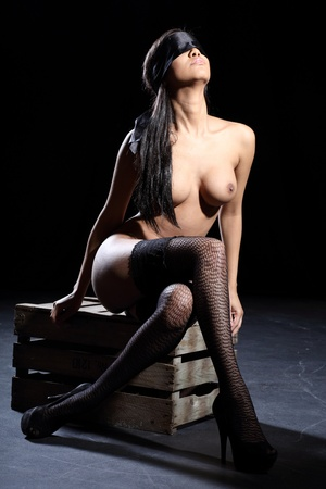 beautiful sexy and fully nude woman is blindfolded with a silk blindfold and she is sitting on a wooden box with a dark background photo