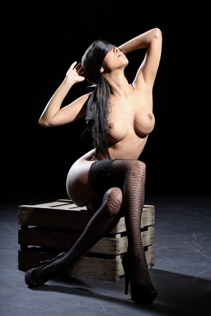 beautiful sexy and fully nude woman is blindfolded with a silk blindfold and she is sitting on a wooden box with a dark background Stock Photo - 13159152