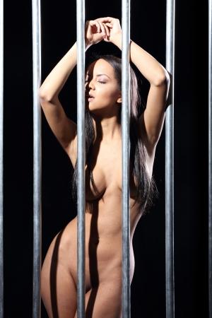 naked: portret van een mooie naakte vrouw in de gevangenis met donkere zwarte achtergrond Stockfoto