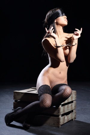 nude woman sitting: beautiful sexy and fully nude woman is bound with a real steel handcuff and blindfolded with a silk blindfold and she is sitting on a wooden box with a dark background Stock Photo