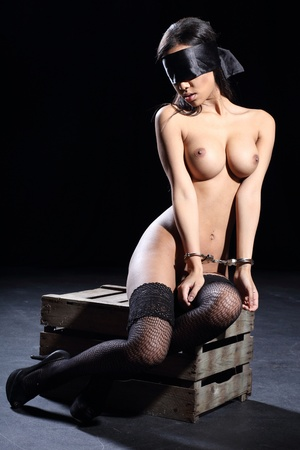beautiful sexy and fully nude woman is bound with a real steel handcuff and blindfolded with a silk blindfold and she is sitting on a wooden box with a dark background Stock Photo