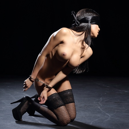very sexy and beautiful woman bound with real steel handcuffs and blindfolded with a silk blindfold Stock Photo