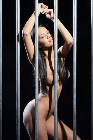 portrait of a beautiful woman in prison with dark black background and steel bars Stock Photo - 13260981