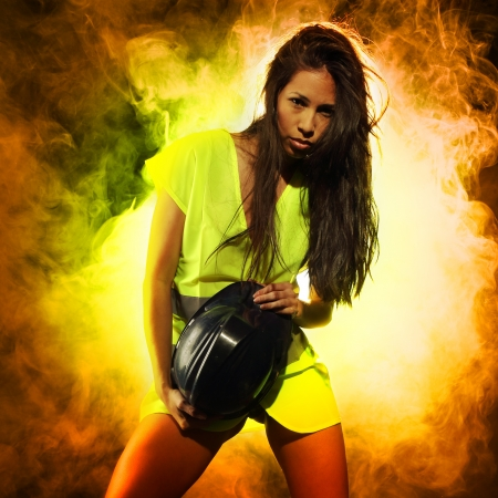 Very beautiful and sexy woman at work wearing a safety or security jacket and behind her smoke Stock Photo