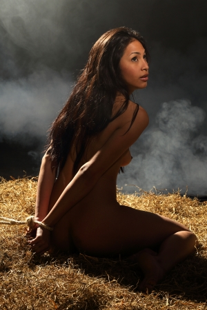 bondage style with a beautiful nude woman who is bound with rope and sitting in a dungeon Stock Photo - 13649225