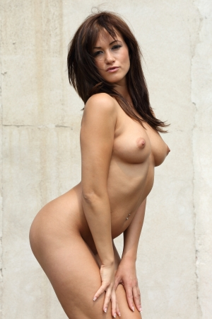 natural looking very sexy and pretty nude woman standing in front of an old wall