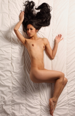 nude in bed: very sexy and beautiful fully nude woman with dark brown hair is posing in bed
