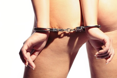 sexy woman tied with handcuffs behind her back showing her beautiful ass