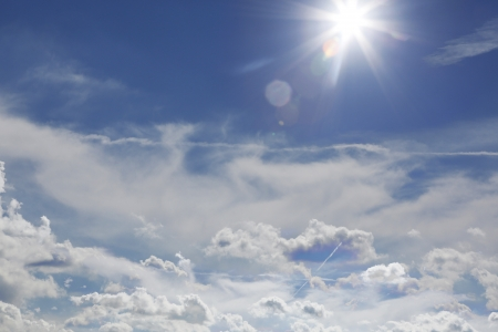 the flair: background of a beautiful blue sky with white clouds and sun flair Stock Photo