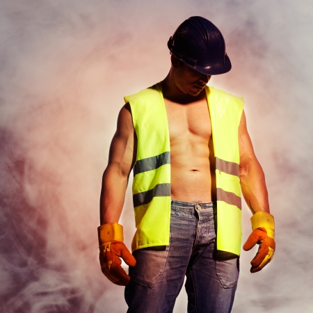 beautiful and sexy man with a great trained bodybuilding body dressed as a construction worker with helmet and gloves and smoke behind him Stock Photo