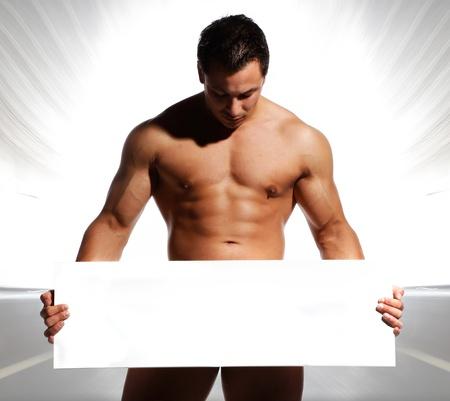 hombre desnudo: hombre de los deportes bella y sexy y bien entrenado está sosteniendo y mostrando un tablero blanco en sus manos se puede escribir texto