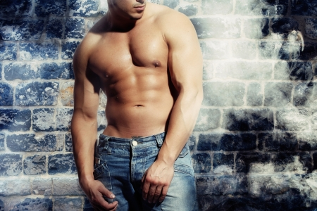 artwork male with a sexy man without a shirt standing against a wall Stock Photo - 14597776