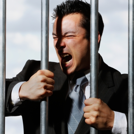 very good looking office manager dressed in a nice suit is screaming behind prison bars photo