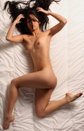 very sexy and beautiful fully nude woman with dark brown hair is posing in bed Stock Photo - 14715281
