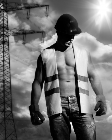 beautiful and sexy man with a great trained bodybuilding body dressed as a construction worker with helmet and gloves and smoke behind him Stock Photo - 14795134