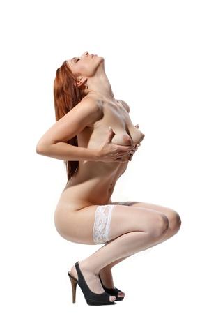 nudo di donna: sexy donna nuda con i capelli rossi e le calze bianche su sfondo bianco