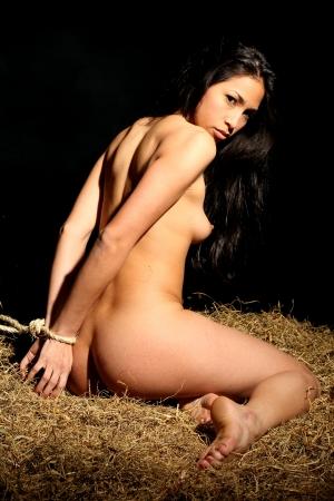 sexo joven: estilo bondage con una hermosa mujer desnuda que est� atado con una cuerda y que se sienta en un calabozo Foto de archivo