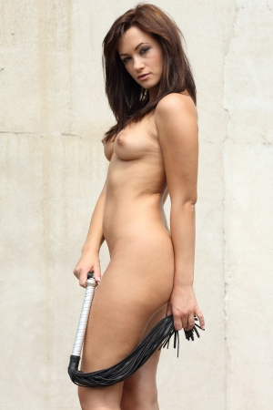 natural looking very sexy and pretty nude woman standing in front of an old wall and holding a whip in her hands