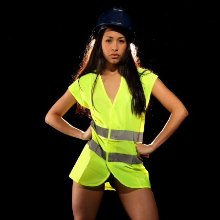 safety vest: Very beautiful and sexy working woman wearing a safety or security jacket or vest and a helmet