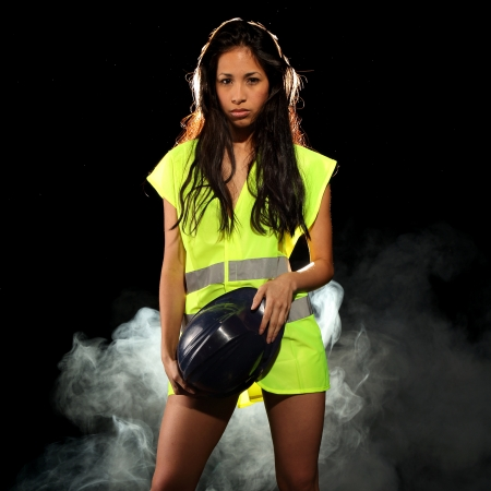 Very beautiful and sexy working woman wearing a safety or security jacket or vest and a helmet photo