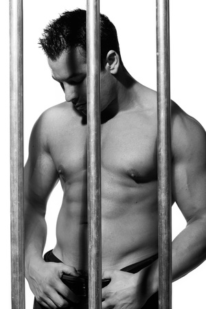 sexy shirtless man behind bars on white background Stock Photo - 16301344