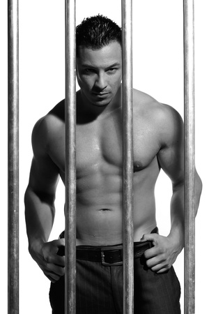 sexy shirtless man behind bars on white background Stock Photo - 16301341