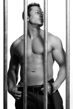 sexy shirtless man behind bars on white background Stock Photo - 16301339