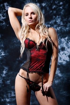 femme tr�s sexy et belle avec de longs cheveux blonds est habill�e en lingerie rouge tr�s agr�able avec soutien-gorge et elle pose dans le style de la mode en face d'un fond de texture flamm�e bleu Banque d'images - 16301319