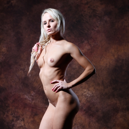 Sexy  woman naked: very sexy and beautiful nude or naked woman with blond long hair is posing in front of a brown flamed textured  background