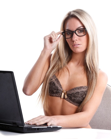 very beautiful woman in lingerie with long blond hair works as secretary with a laptop computer on a white desk and background