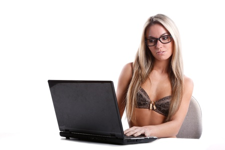 very beautiful woman in lingerie with long blond hair works as secretary with a laptop computer on a white desk and background Stock Photo - 16753661