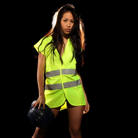 sexy construction worker: Very beautiful and sexy working woman wearing  a safety or security jacket or vest and a helmet