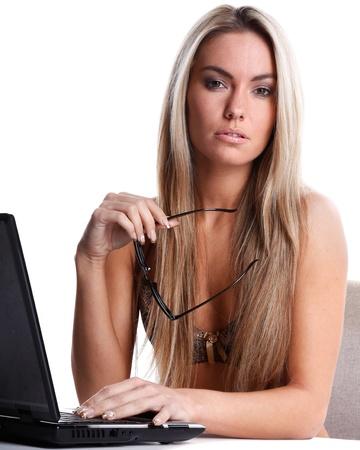 secretaria: hermosa mujer en ropa interior con el pelo largo y rubio trabaja como secretaria con un ordenador port?l en un escritorio blanco y el fondo Foto de archivo