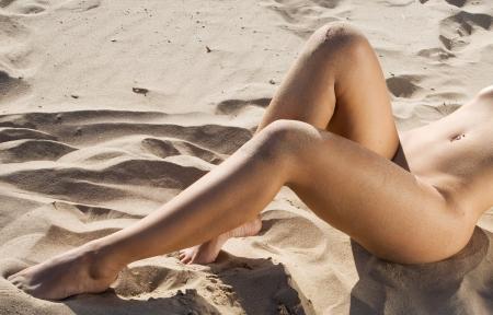 nue plage: parties du corps d'une femme nue sur une plage Banque d'images