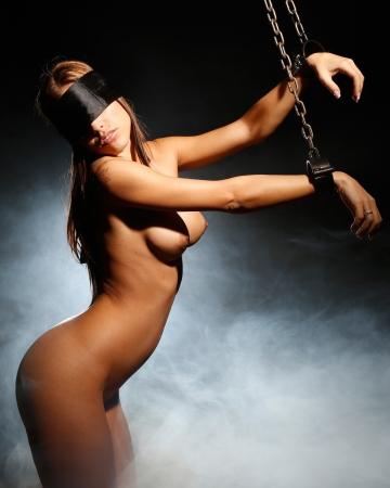 girl sexy nude: mujer desnuda o desnudo muy sexy atado en servidumbre cincuenta tonos de gris estilo con grilletes de hierro medievales y pu�os y ella tiene los ojos vendados con una venda de seda y detr�s de ella humo y luces
